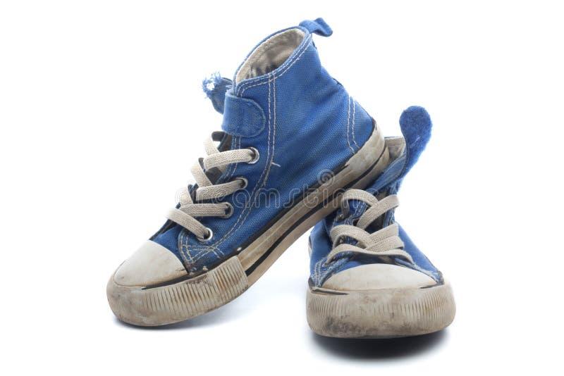 Pares de sapatilhas azuis sujas, gastadas das crianças imagens de stock