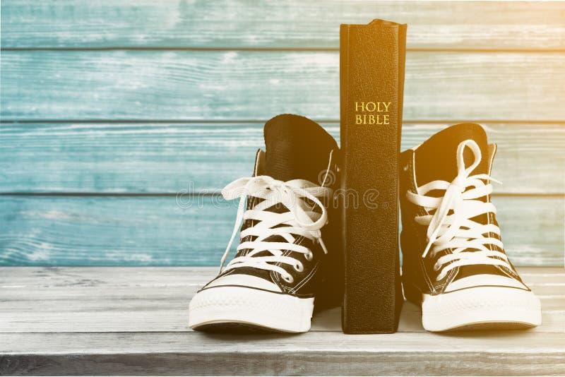 Pares de sapatilhas e de Holly Bible pretas novas fotografia de stock royalty free