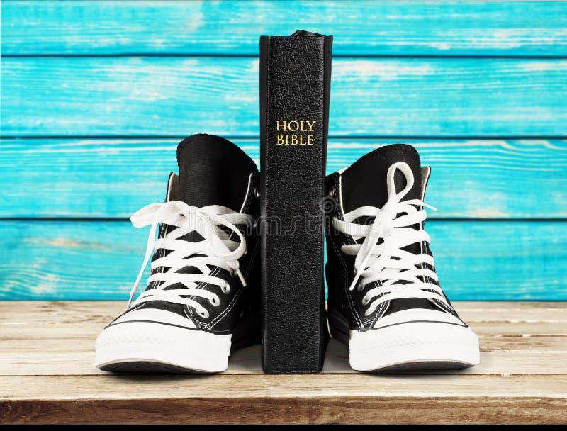 Pares de sapatilhas e de Holly Bible pretas novas foto de stock royalty free