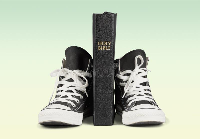 Pares de sapatilhas e de Holly Bible pretas novas foto de stock