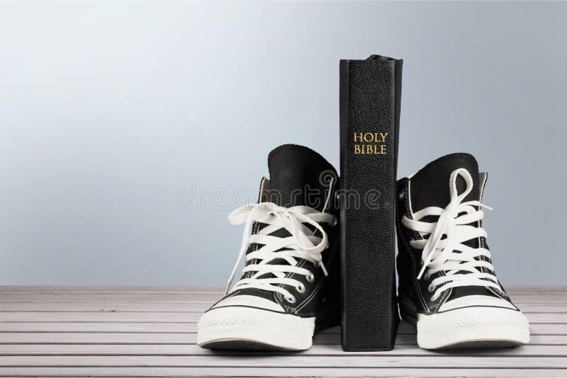 Pares de sapatilhas e de Holly Bible pretas novas imagens de stock royalty free