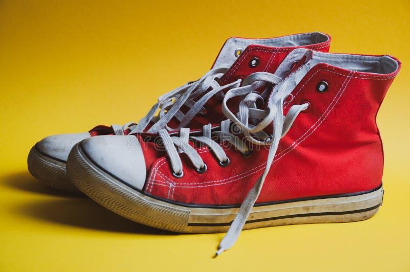 Pares de sapatilhas usadas vermelhas no fundo colorido amarelo, vista do lado foto de stock