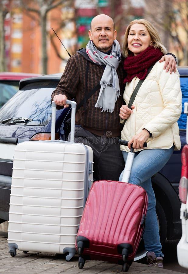 Pares de Seniorpleasant de los viajeros que presentan con los curricaneros imágenes de archivo libres de regalías