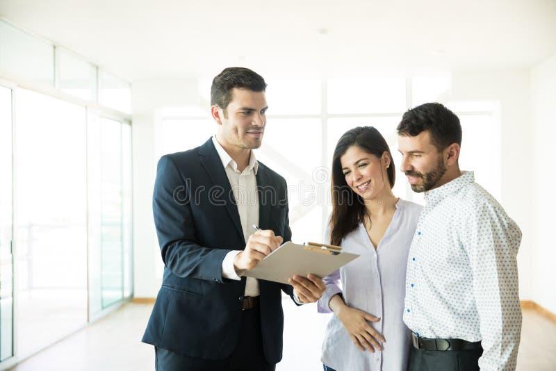 Pares de Showing Contract To do agente na casa nova foto de stock