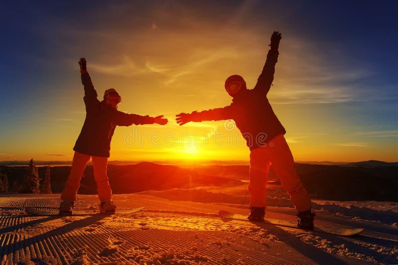 Pares de snowboarders en la montaña foto de archivo