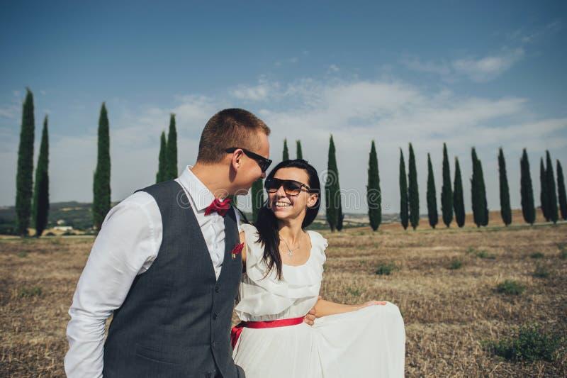Pares de sorriso à moda felizes que andam e que beijam em Toscânia, AIE foto de stock