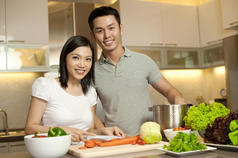 Pares de sorriso asiáticos na cozinha fotos de stock