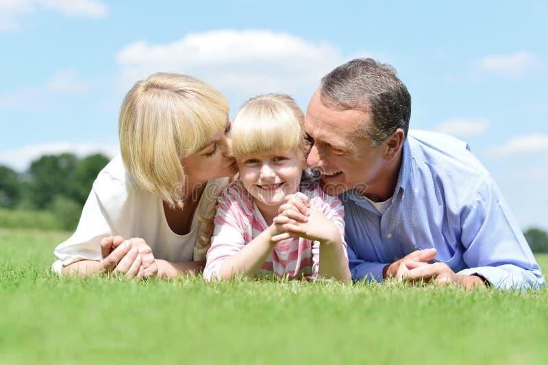Pares de sorriso com a filha que levanta em fora imagens de stock royalty free