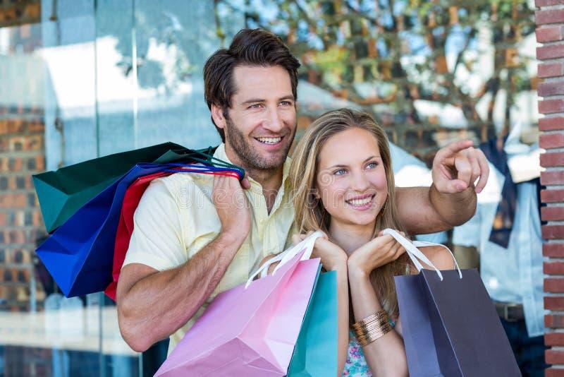 Pares de sorriso com os sacos de compras que olham e apontar foto de stock