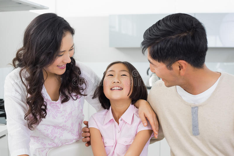 Pares de sorriso com uma filha alegre na cozinha fotografia de stock