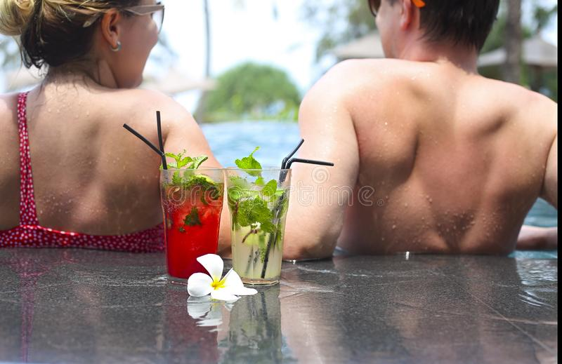 Pares de sorriso com vidros de cocktail do álcool perto da piscina imagem de stock royalty free