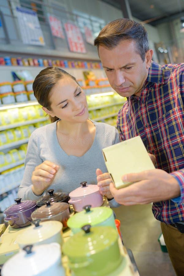 Pares de sorriso da família que compram utensílios de mesa cerâmicos no cookware da loja imagens de stock royalty free