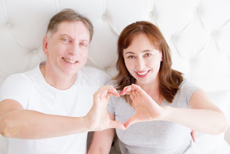 Pares de sorriso da Idade Média que mostram o sinal do coração pelos braços no quarto Conceito do relacionamento do amor e da vid imagens de stock royalty free