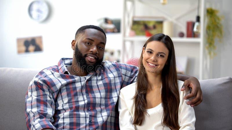 Pares de sorriso da misturado-raça que sentam-se no sofá em casa e em olhar a câmera, família fotos de stock