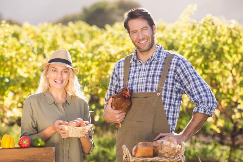 Pares de sorriso do fazendeiro que guardam a galinha e os ovos fotografia de stock royalty free