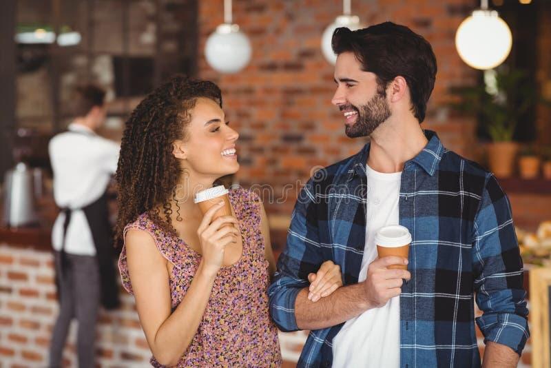 Pares de sorriso do moderno com copos afastados imagens de stock royalty free
