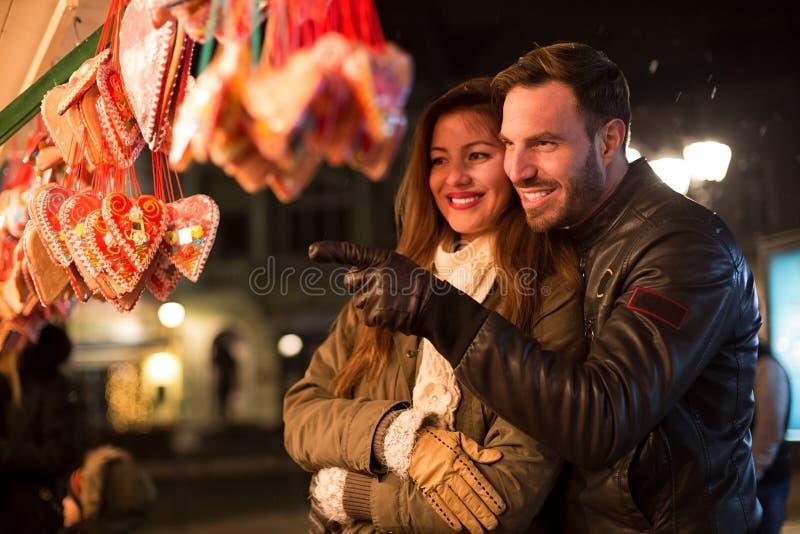 Pares de sorriso felizes que olham corações dos doces no feriado do Natal imagem de stock royalty free