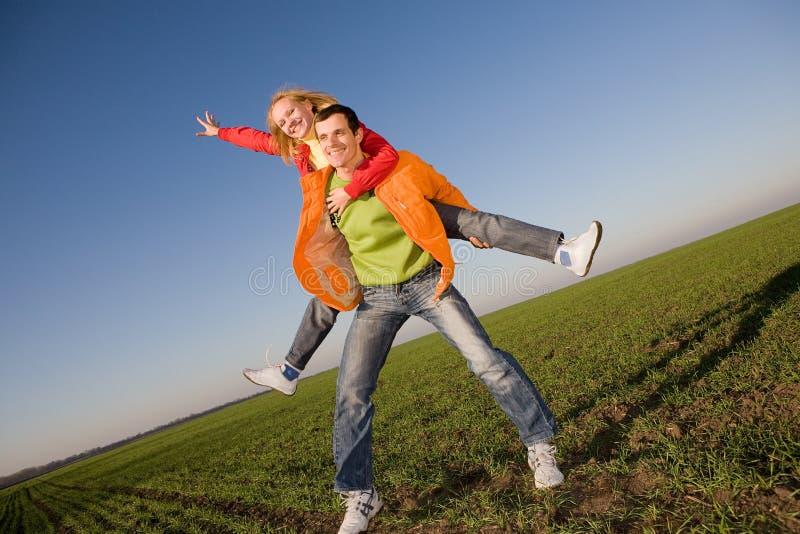 Pares de sorriso felizes que saltam no céu fotografia de stock royalty free