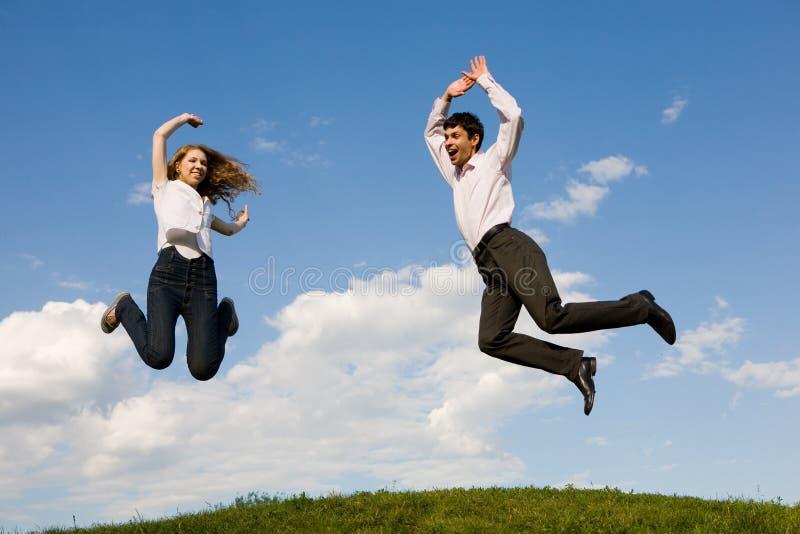 Pares de sorriso felizes que saltam no céu azul imagem de stock royalty free