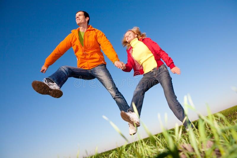 Pares de sorriso felizes que saltam no céu azul fotografia de stock