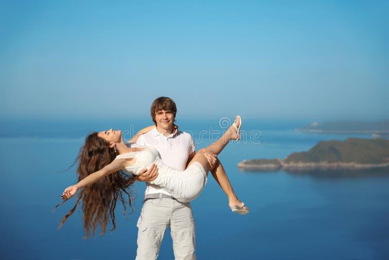 Pares de sorriso felizes que têm o divertimento sobre o fundo do céu azul Enjoym fotos de stock royalty free