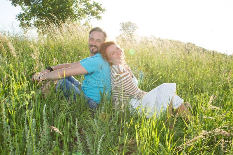 Pares de sorriso na grama do verão no por do sol homem feliz e mulher que sentam-se no campo de volta à parte traseira fotografia de stock royalty free