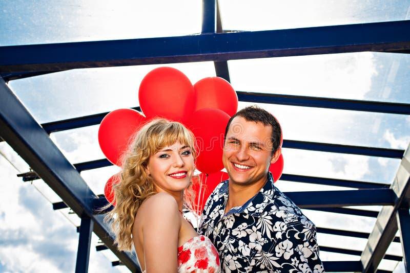 Pares de sorriso novos com balões vermelhos fotografia de stock