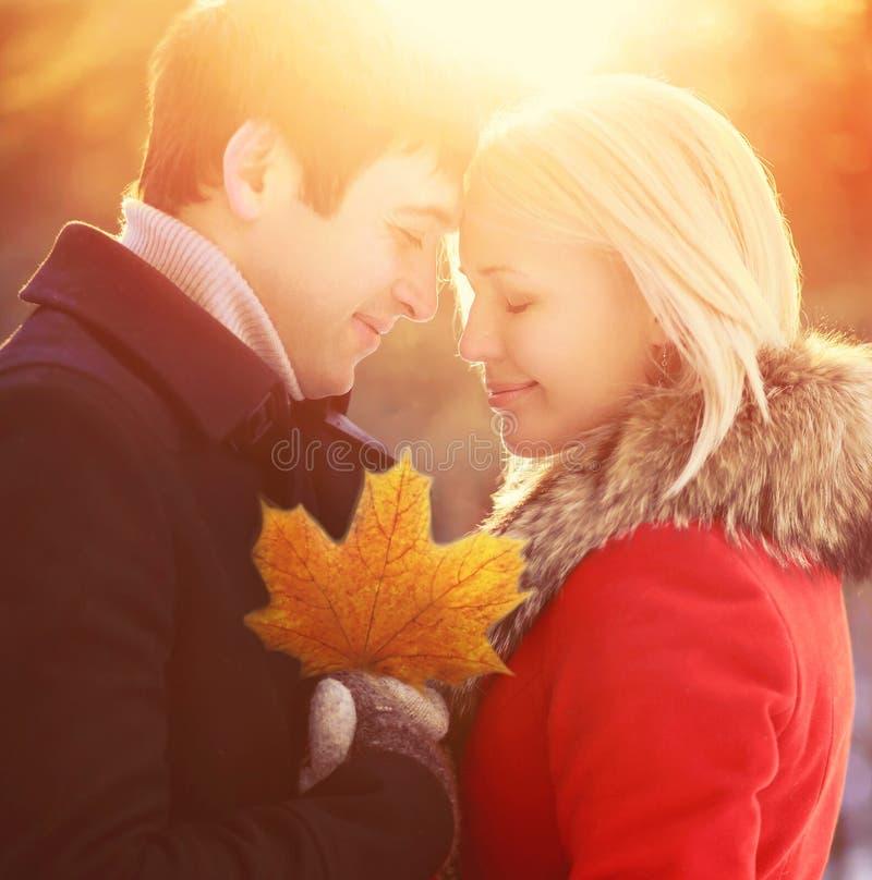 Pares de sorriso novos felizes do retrato ensolarado no amor com folha de bordo do outono fora no por do sol morno fotos de stock royalty free