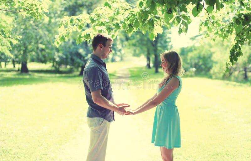 Pares de sorriso novos felizes no amor, mãos das posses, relacionamentos, data, casamento - conceito, cores macias do vintage fotos de stock