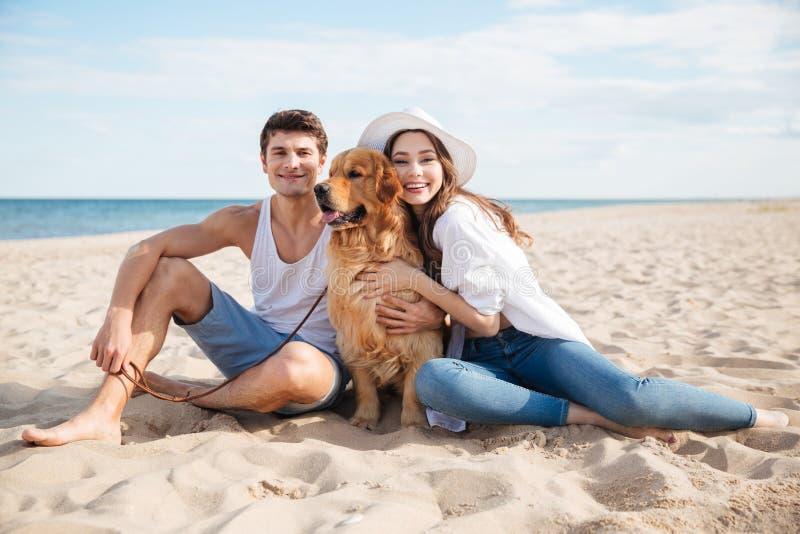 Pares de sorriso novos no amor que senta-se na praia com cão imagem de stock royalty free