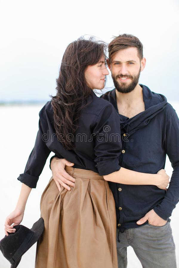 Pares de sorriso novos que abraçam-se e que vestem a roupa elegante no fundo monofônico branco do inverno foto de stock