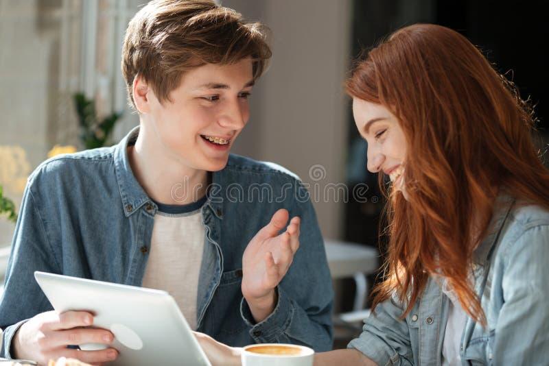 Pares de sorriso novos que falam ao usar a tabuleta imagem de stock royalty free