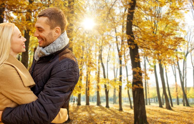 Pares de sorriso que abra?am no parque do outono imagens de stock
