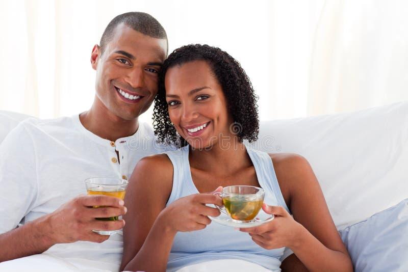 Pares de sorriso que bebem um copo do chá em sua cama. imagem de stock