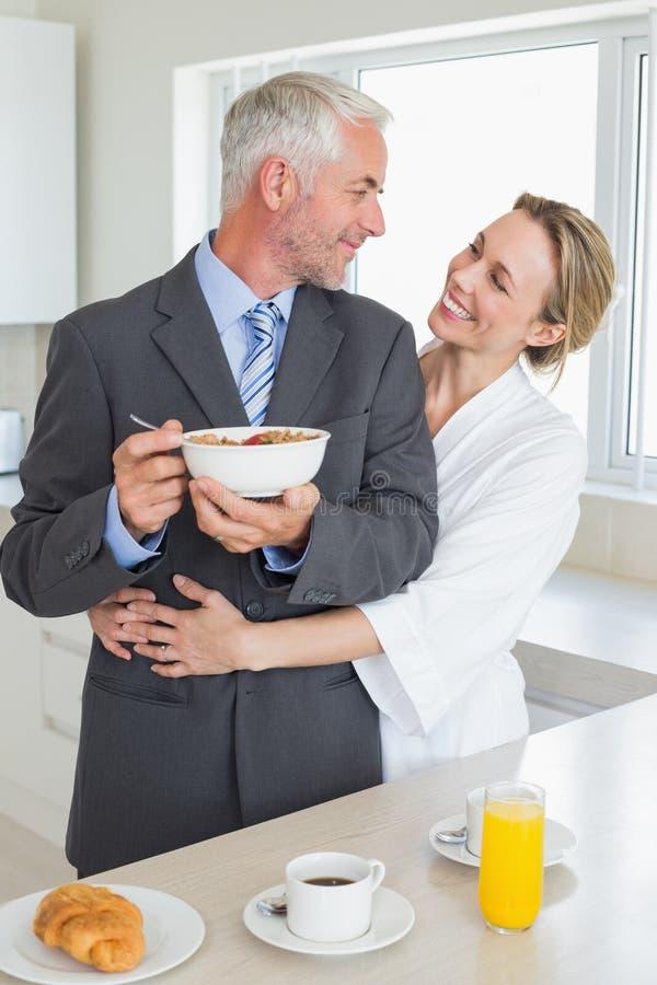 Pares de sorriso que comem o café da manhã na manhã antes do trabalho imagens de stock royalty free