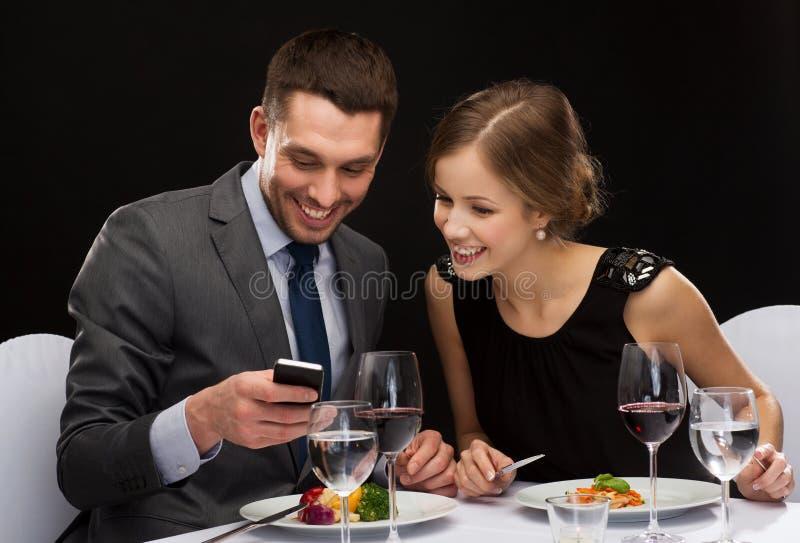 Pares de sorriso que comem o prato principal no restaurante imagens de stock royalty free