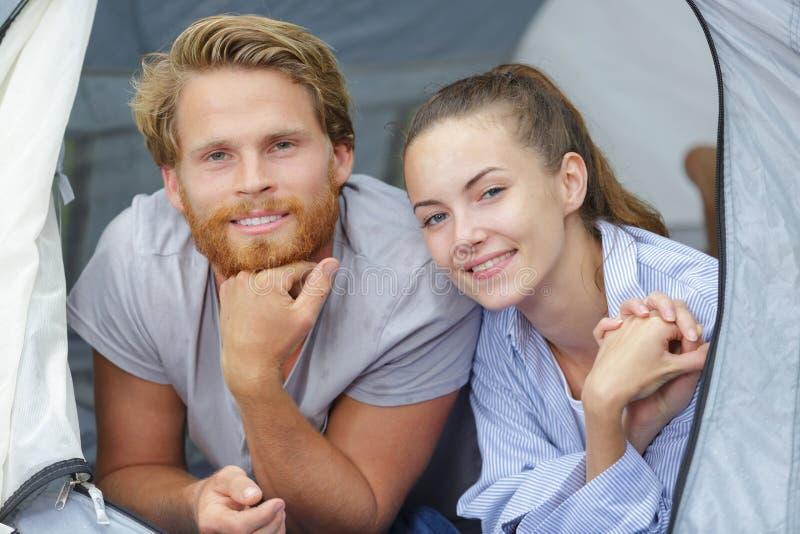 Pares de sorriso que descansam na barraca de acampamento fotos de stock