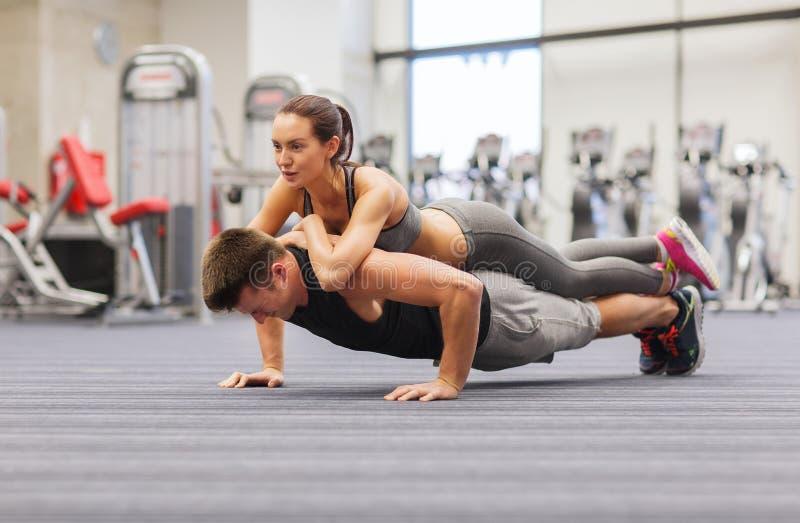 Pares de sorriso que fazem impulso-UPS no gym fotos de stock royalty free