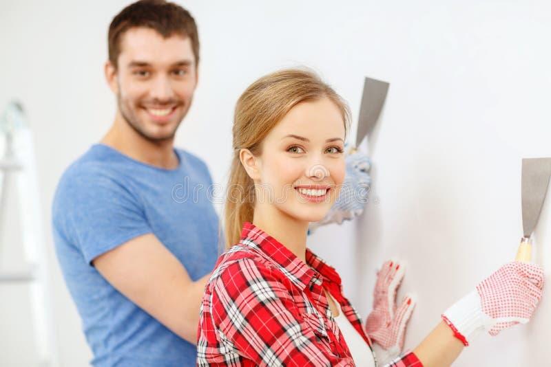 Pares de sorriso que fazem renovações em casa fotografia de stock