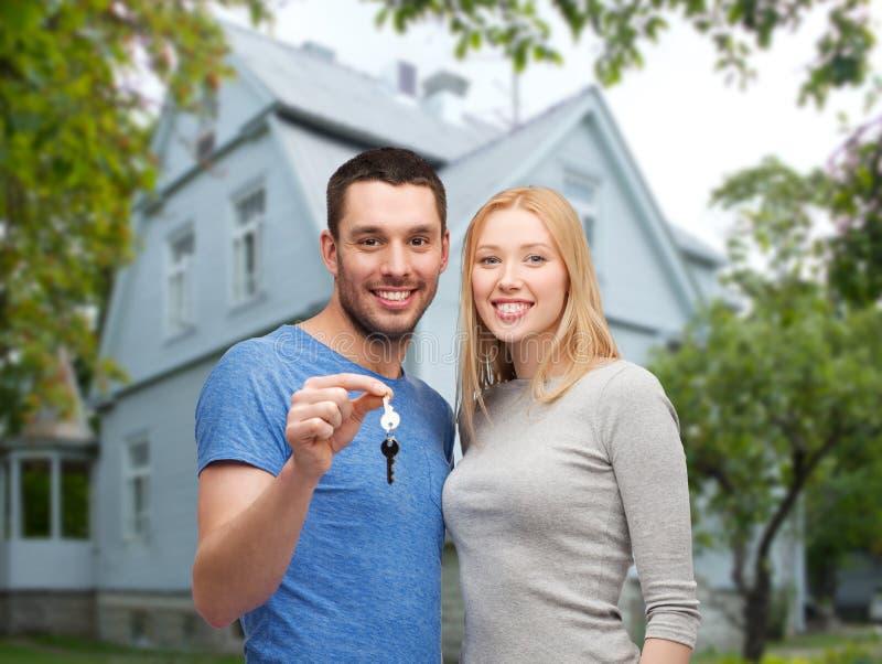 Pares de sorriso que mostram a chave sobre o fundo da casa imagens de stock