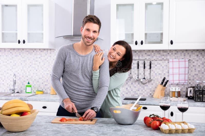 Pares de sorriso que preparam o alimento na cozinha foto de stock royalty free