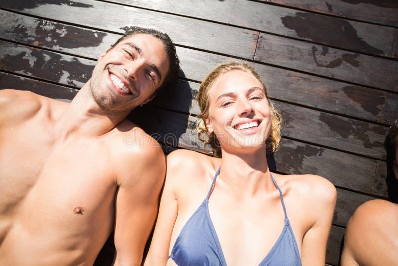 Pares de sorriso que relaxam na plataforma de madeira fotografia de stock