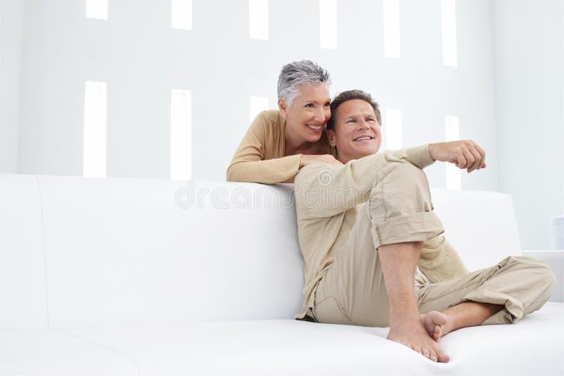 Pares de sorriso que relaxam na sala de visitas fotografia de stock