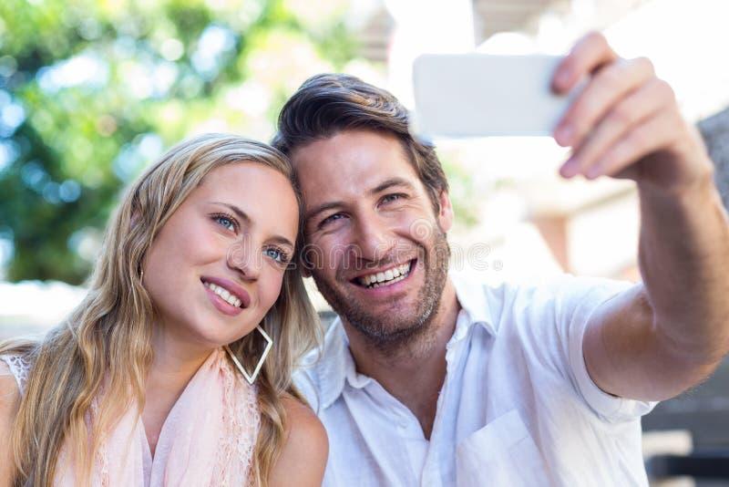 Pares de sorriso que sentam e que tomam selfies fotografia de stock