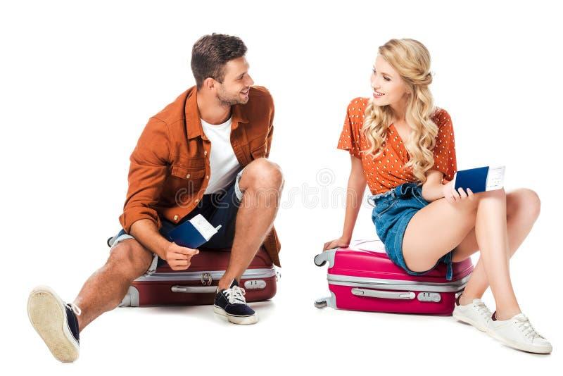 pares de sorriso que sentam-se em sacos do curso com passaportes e bilhetes imagens de stock royalty free
