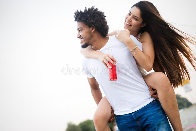 Pares de sorriso que t?m o divertimento sobre o fundo do c?u Conceito dos feriados, das f?rias, do amor e da amizade imagem de stock