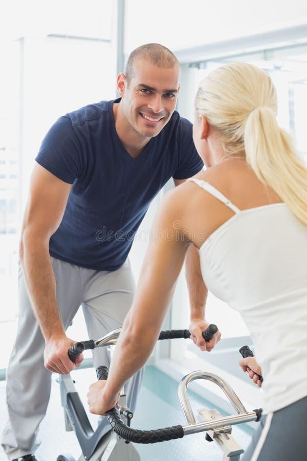 Pares de sorriso que trabalham em bicicletas de exercício no gym foto de stock
