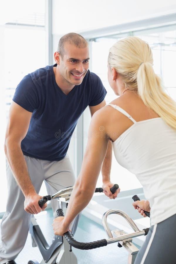 Pares de sorriso que trabalham em bicicletas de exercício no gym fotografia de stock