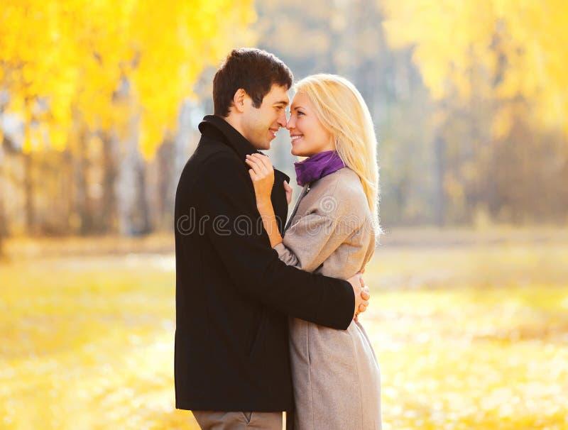 Pares de sorriso românticos do retrato no amor no dia ensolarado morno sobre as folhas amarelas foto de stock