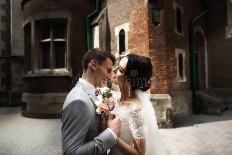 Pares de sorriso de surpresa do casamento Noiva bonita e noivo à moda perto da igreja imagem de stock royalty free